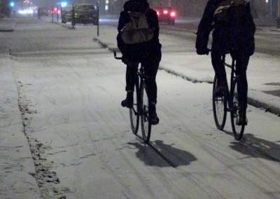 Des cyclistes d'hiver roulant sur une bande cyclable séparée de la circulation automobile à Montréal